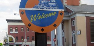 """A round blue and orange sign on an urban street corner with a train on it reads """"Welcome to the Ironbound"""""""