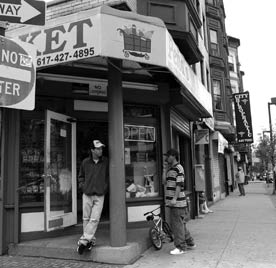 A black-and-white photograph showing a street-corner scene in Boston. A man leans on a pillar outside a market, while another looks in the window. Illustrating an article about eminent domain.