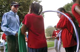 Photo shows a man at left talking to children wearing red shirts and holding towels and hula hoops, to accompany an article about youth violence.