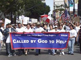 """Photo shows a group of people marching behind a blue banner that says """"Called by God to Help."""" Accompanying article on faith-based community organizing."""