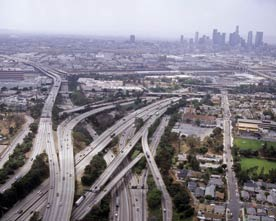 photo is an aerial view of Los Angeles and shows several highways crossing over and under one another, merging and dividing; accompanying an article on urban policy