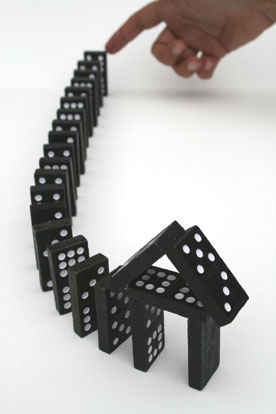 image shows a finger about to set a row of dominoes to toppling, as a metaphor for the foreclosure crisis.