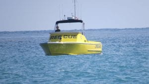 """photo of a yellow rescue boat, surrounded by blue water, to illustrate article on """"rethinking the rescue"""""""