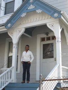 photo shows Roslyn George on the front porch of her home, purchased with the help of the Massachusetts Affordable Housing Alliance