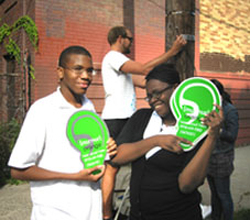 Photo shows people holding up large green ears, symbols of the Murmur project, in Orange NJ