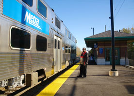 Photo shows person waiting to board a train at a Chicago-suburb station.