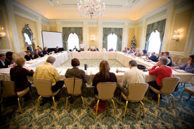 nonprofit housing development. Image is of a large table of people at a conference