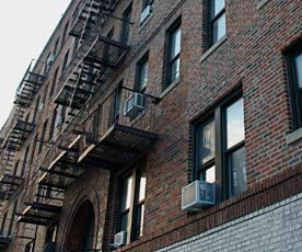Image shows front of apartment building; predatory equity