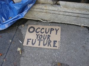 """Occupy: Image shows cardboard sign reading """"Occupy your Future"""""""
