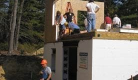 Several workers stand on a partially finished home with white insulation around the foundation.
