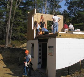 Several workers stand on a partially finished home with white concrete foundation forming a basement floor and insulated panels forming one corner of a first floor.