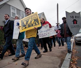 City Life/Vida Urbana: image shows a group marching through the streets of Hyde Park, Mass.