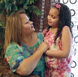 Image shows a mother holding her young daughter, who has asthma