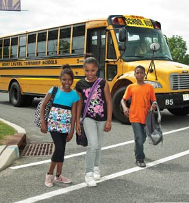 Mount Laurel. Photo shows schoolkids standing by a school bus