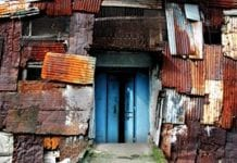 In the center are blue doors that are surrounded by orange, white, and brown pieces of metal-looking material. This is what a warehouse looks like in a Mumbai slum.
