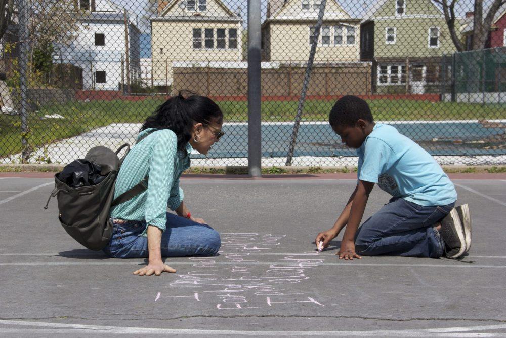 A boy writes haiku on the pavement with chalk