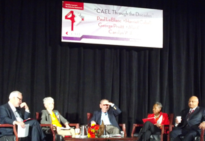 Photo shows a panel of five people on a stage under a banner that announces the CAEL conference.