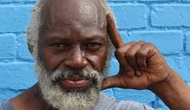 """Close up of an African-American Vietnam veteran with white beard standing in front of a bright blue walk, and holding his hand up to the left side of his face in an """"L"""" shape."""