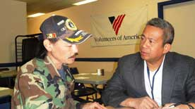 A man in camouflage jacket an hat talks at a table with a man in a suit, with a Volunteers of America banner on the wall behind them.