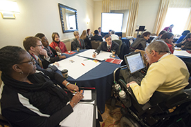 A multiracial group of people around a conference table, with a person using a wheelchair and an assistive communication device in the foreground