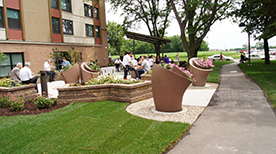 Seniors sit in small groups in an outdoor plaza, surrounded by planters of flowers, with an apartment building visible in the background.