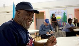 A smiling African-American man in a baseball cap sits at a table in a social lounge type room with other people in the background.