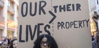"""A woman holds a cardboard sign that reads """"Our Lives > Their Property"""""""