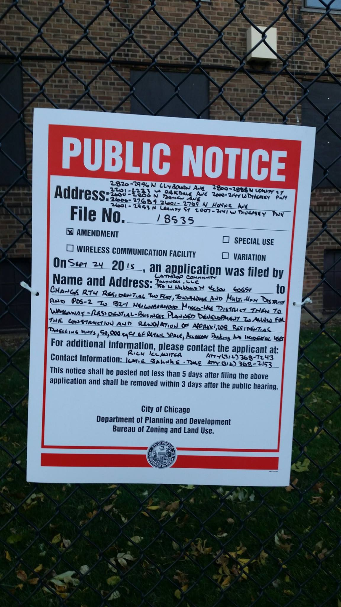 A close up of public notice of an intent to file a zoning change for Lathrop Homes in Chicago, attached to a wire fence