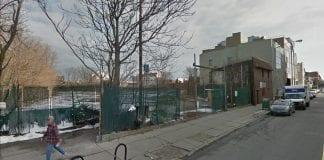 A fenced lot on a city street.