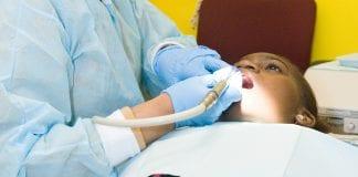 A female dentist cleans a young boy's teeth.