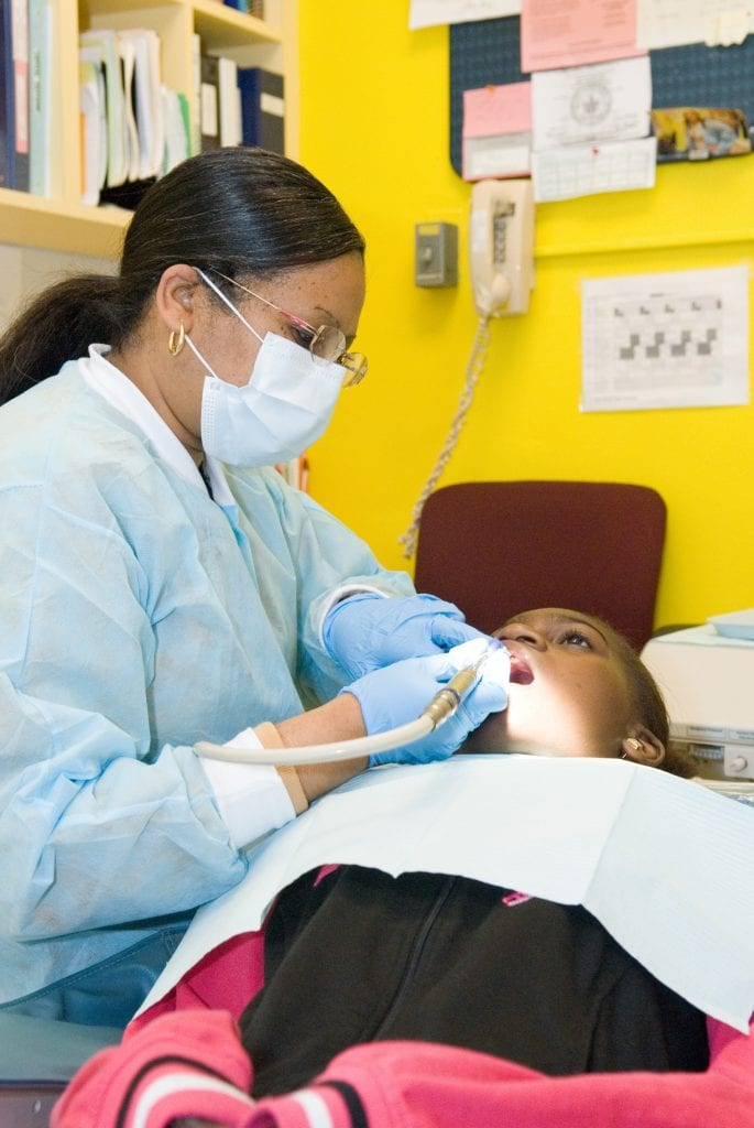 A female dentist cleans a young boy's teeth.