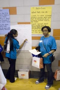 Two students wearing blue shirts stand in front of posters in their school.