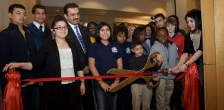 A group of people stand behind a red ribbon before the opening of an art exhibit at a charter school. To the right, youngsters prepare to cut the ribbon with large scissors.