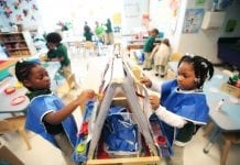 Two young students wear smocks as they paint in school.