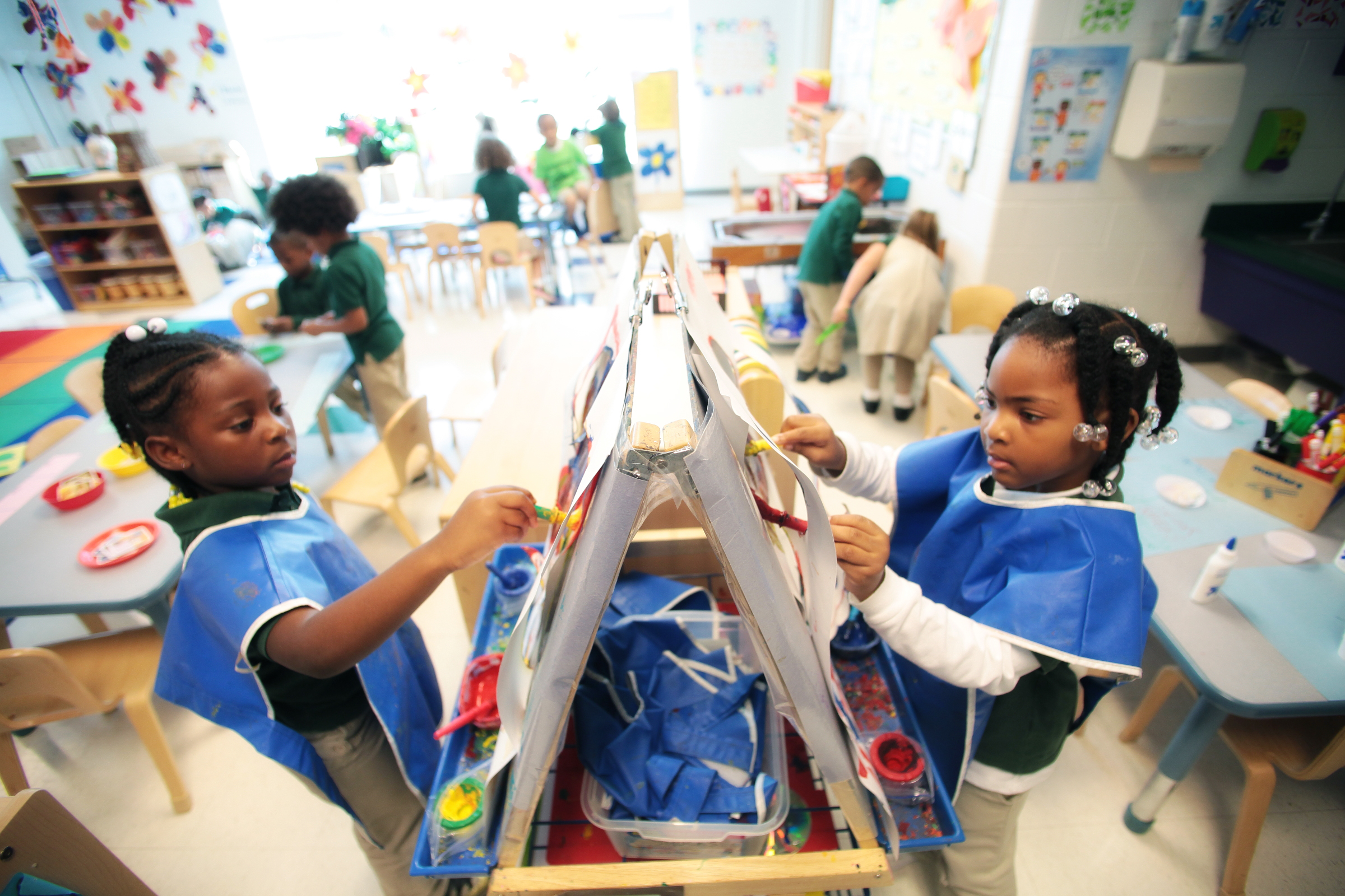 Two young students wear blue smocks as they paint a picture. The young African-American students are in a classroom at the Drew Charter School in Atlanta.