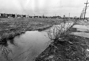 An empty lot, bordered by houses on the left and utility poles on the right. In the center is a ditch which has accumulated water. The site is a lot on which the Whitman Park Houses were built.