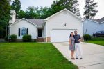 A woman and man stand together smiling in front of their new home in North Carolina. They received a loan not based on credit scores, but on character.