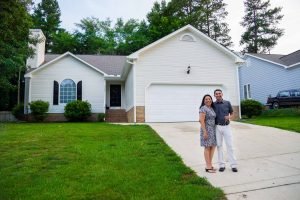A woman and man stand together smiling in front of their new home in North Carolina.
