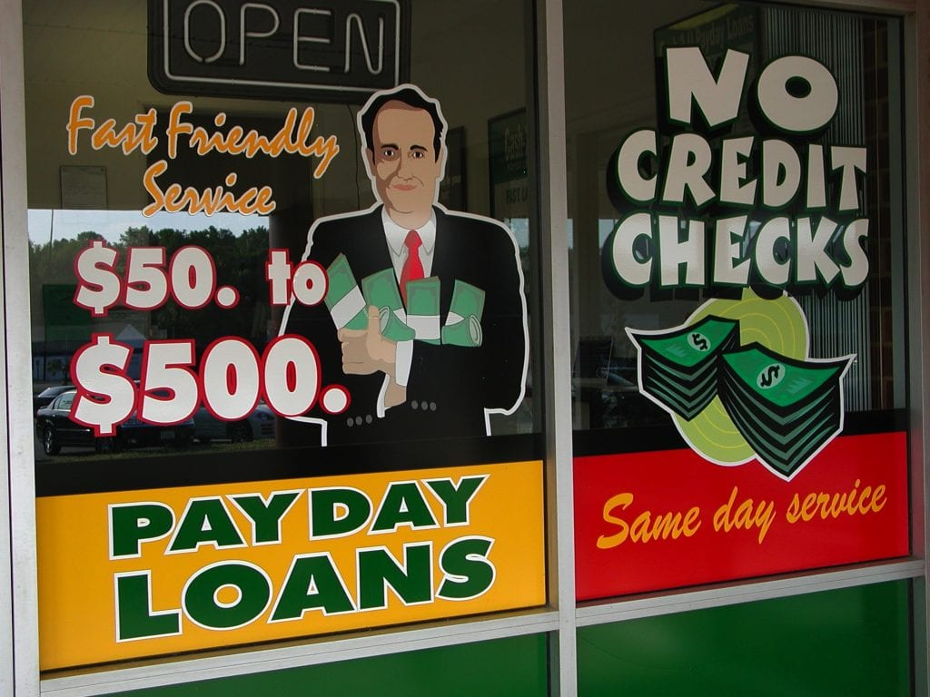 "A sign for payday loans is seen on a window, with a illustration of a man in a suit holder cash in his arms. The sign also reads ""Fast friendly service. $50 to $500."""