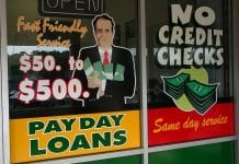 """A sign for payday loans is seen on a window, with a illustration of a man in a suit holder cash in his arms. The sign also reads """"Fast friendly service. $50 to $500."""""""