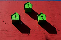 small green birdhouses on red wall