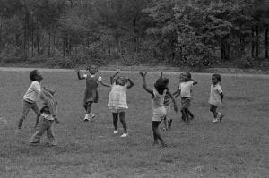 A black and white photo of children playing at New Communities in Georgia, the largest African-American owned parcel of land in the U.S. in the 1960s.