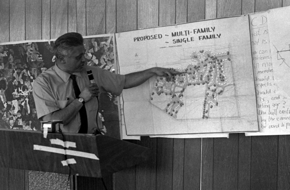 A black and white photo of a man pointing to a design of a multi-family residences called New Communities.
