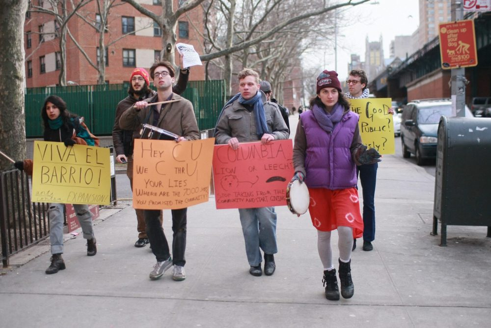College students walk down a street in Harlem holding signs that show their displeasure with Columbia University. Some students are playing musical instruments.