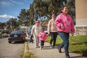 "A woman in a pink, ""I love San Francisco"" sweater walks ahead of two women in light beige sweaters and a little girl who is wearing a pink coat and drinking a bottle of water. They are walking down a street and passing a black car that is parked on the left."