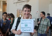 """A woman holds a sign outside of the Oakland City Council chambers that reads """"Democratic Workplaces equal Democratic Oakland!"""""""