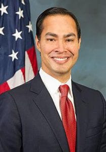 A man, who is wearing a red tie, white shirt, and a dark colored jacket, smiles. In the background, there's a partial view of the American flag. Less than 10 stars and partial red and white strips can be seen.