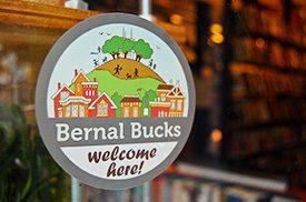 A sticker on a window promotes Bernal Bucks, a business initiative in San Francisco.