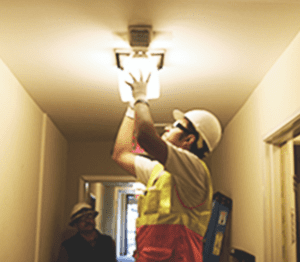 A trainee wearing a white hardhat fixes a light fixture in an apartment.