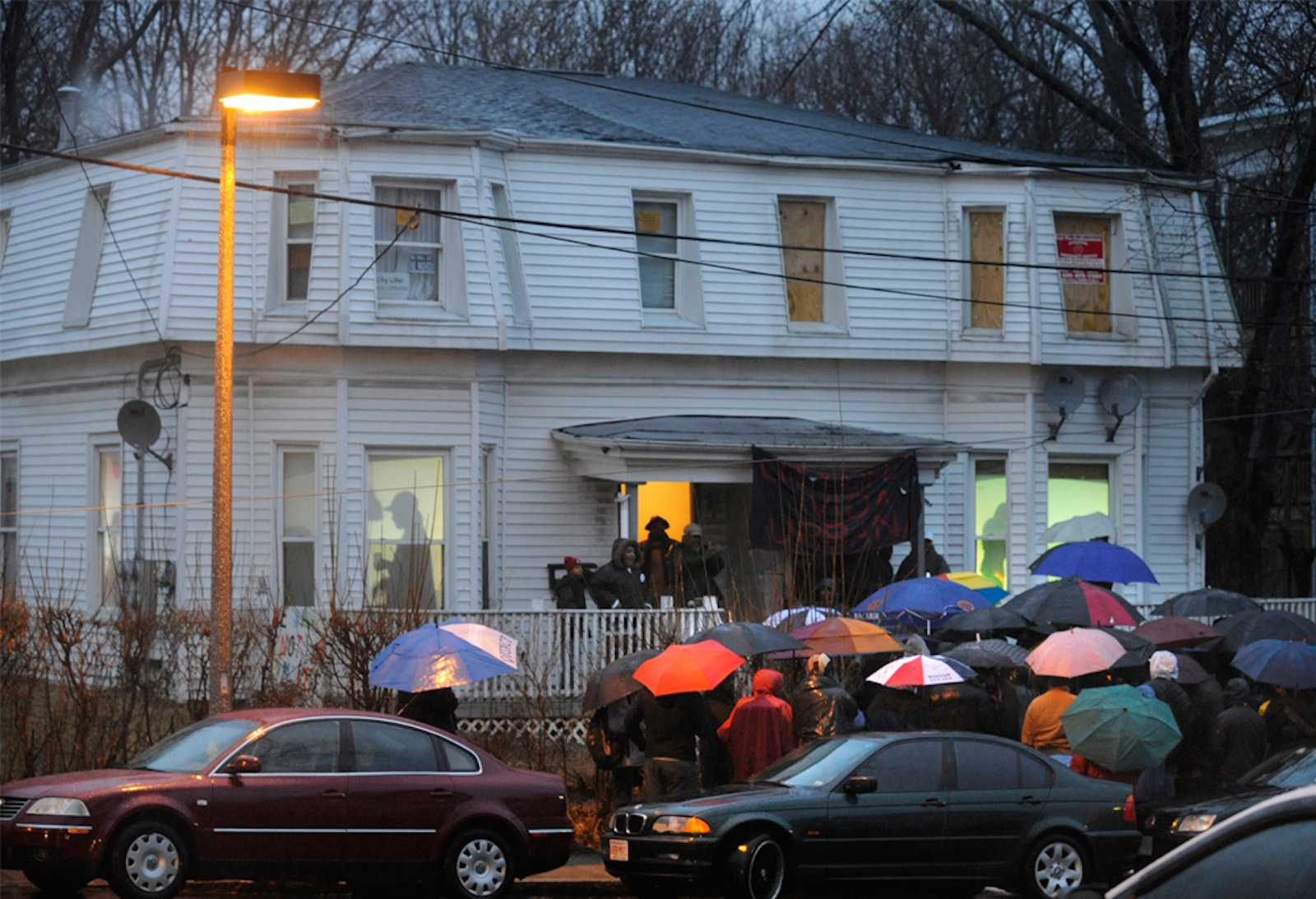 People stand outside of a home in the rain while a projection of people are shown inside. This was part of an art installation in Boston.
